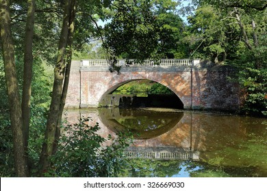 Red Brick Bridge over a lake in an English park