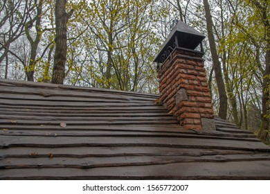 A red brick chimney with four pitched wrought iron peak above it and wrought iron curlicues on a wooden plank roof on a rainy autumn day against trunks and branches of trees and a gloomy cloudy sky