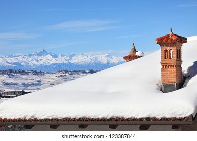 Red brick chimney on the roof covered by snow and snowy mountains on the background under blue winter sky in Piedmont, Northern Italy.