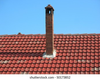 Red brick chimney on tile roof over blue sky background