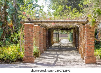 Red brick collumn alley-way pergola entrance with romantic tropical plants on a bright summer day in Port Elizabeth in South Africa.