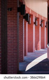 red brick columns curving around pathway in playful light