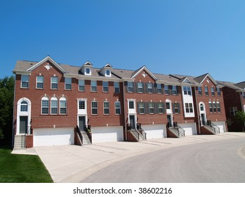 Red brick condos or town homes with the garage in the front.
