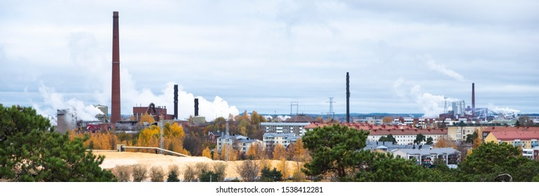 Red brick factory chimneys with smoke. Cardboard factory in Finland, the city of Kotka. The complex of buildings of the old factory.