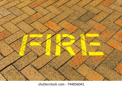 the red brick floor with yellow word fire for abstract background.
