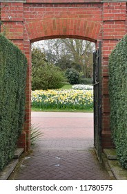 Red Brick Gateway looking out to a Vista of Spring Flowers