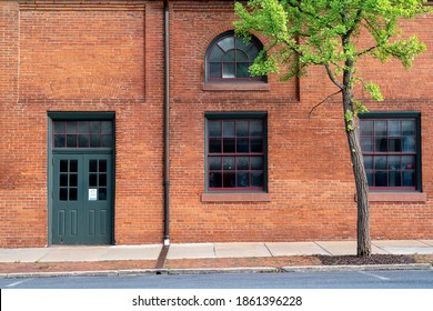 A red brick industrial building in the city city with a green entrance door.