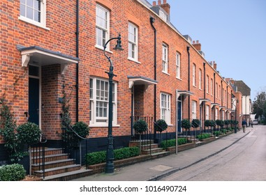 Red brick modern architecture terrace houses (row houses) with a retro, vintage Victorian style. There a old fashion style street lamps , sash window and steps with railings leading to the front door