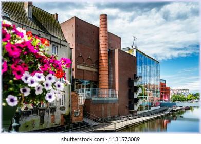 Red brick modern building in Mechelen, Belgium. View from the bridge over the river Dijle