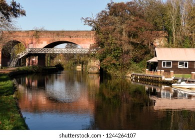 A red brick railway bridge reflected in the still waters of the Wey in Guildford, Surrey