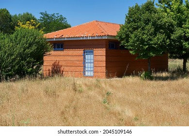 red brick shed with white wooden door protected by blue metal grate door with weeds in the foreground