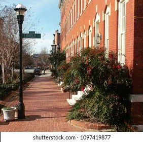 Red, brick sidewalk in front of three-story rowhouses, located in Bolton Hill neighborhood of Baltimore.