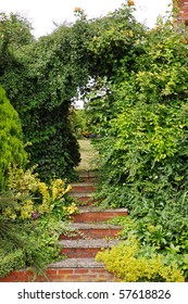 Red Brick Steps leading under an archway into an English garden