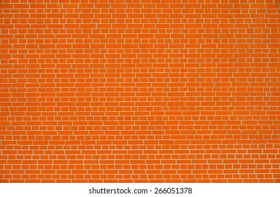 Red brick wall background on sunny summer day.