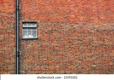 red brick wall background with small window and copy space