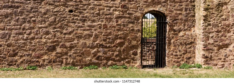 Red brick wall with a barred door