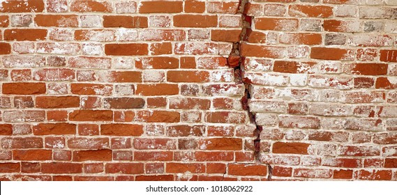 Red Brick Wall With A Big Crack. Damaged  Stonewall Texture. Cracked Dark Old Brick Wall Texture. Ruinous Brickwall Dilapidation Background.