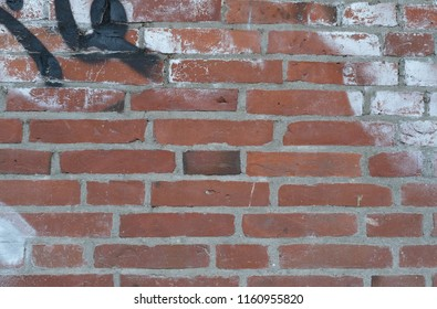 Red brick wall with graffiti as a background