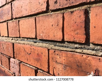 Red brick wall with old fashioned slate damp proofing
