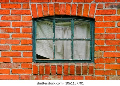 Red brick wall with old weathered window