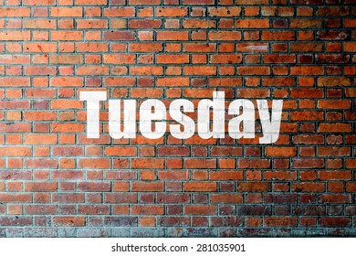 Red Brick wall texture background with a word Tuesday