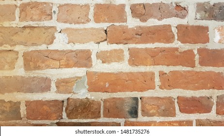 Red brick wall with thick mortar, misshaped bricks and a crack starting middle top down to the left hand corner.