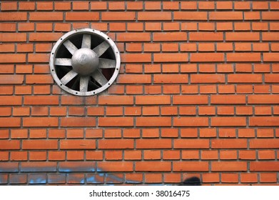 Red brick wall and ventilation propeller.