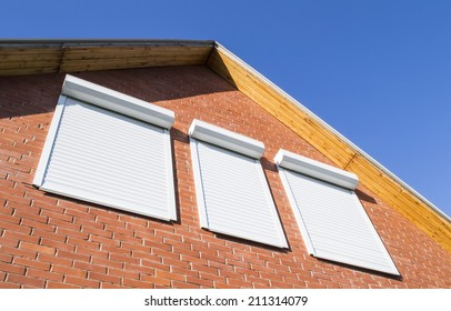 Red brick wall and window with rolling shutters