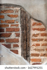 Red Brick Wall with Wood Support Beam Behind Concrete Wall