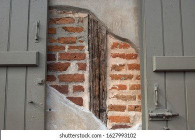 Red Brick Wall with Wood Support Beam Behind Concrete Wall Behind Grey Door Gate
