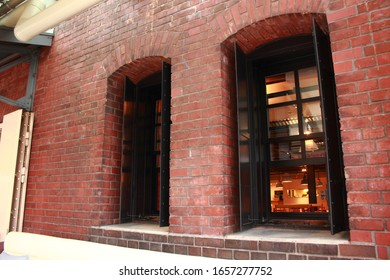 Red brick warehouse's window, can see through cafe.