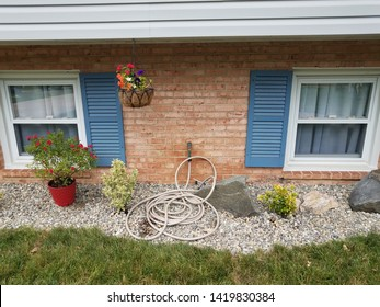 red bricks, blue shutters, garden hose and stones