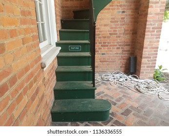 red bricks with green stairs and sign that says staff only