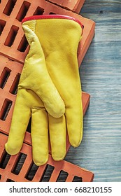 Red bricks leather safety gloves on wooden board top view buildi