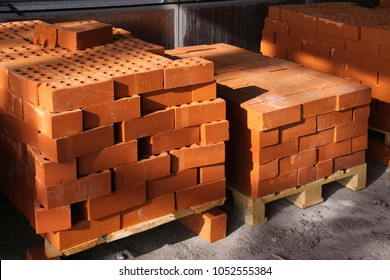 Red bricks are stacked into cubes. red blocks of brick in stock. Warehouse bricks. Storage of products made of bricks.
