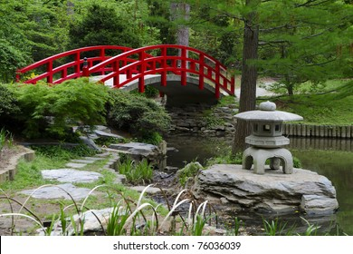 Red bridge in Japanese style garden on gray day
