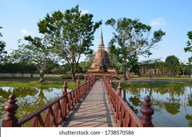 A red bridge is leading to Wat Sra Sri, a beautiful temple in the historical park of Sukhothai