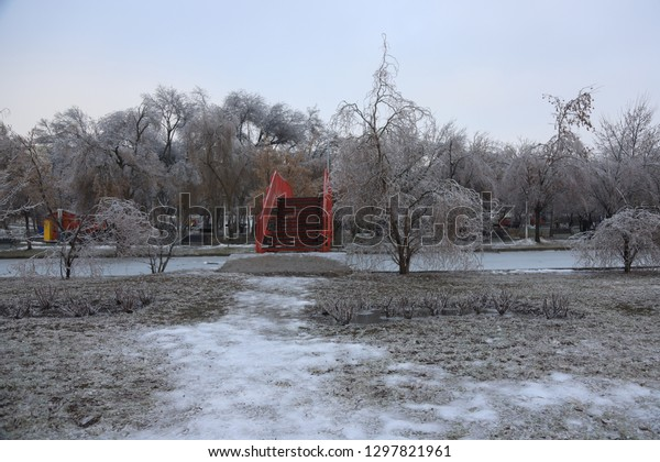Red bridge over icy waterway surrounded by iced trees