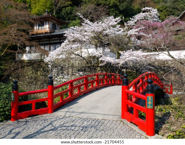 Red bridge and traditional old building on the mountain side with spring cherry blossoms near the famous Minoh waterfall sightseeing spot