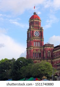 Red British colonial clock tower building. The original building of the Yangon High Court in Myanmar.