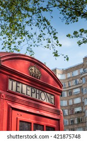Red British Phone box with art deco building in background