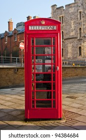 Red British telephone box in front Windsor castle