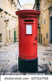 Red British vintage post box in a cobblestone street in Valletta, Malta
