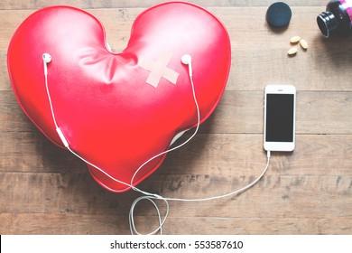 red broken heart with bandage listening music on mobile phone, Broken heart concept on wood floor