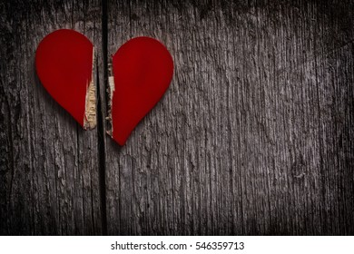 red broken heart on old grungy wooden background - dark and moody