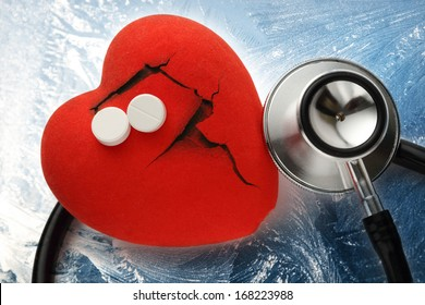 Red broken heart, stethoscope and pills on ice