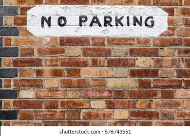 Red and Brown Brick Wall with White No Parking Painted Sign in London, England