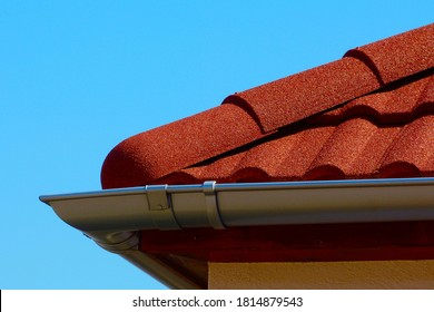 red brown color sandy textured modern concrete roof tile closeup detail with half round ridge tiles. light gray silver shallow zink gutter. house construction concept. light blue sky background.   - Shutterstock ID 1814879543