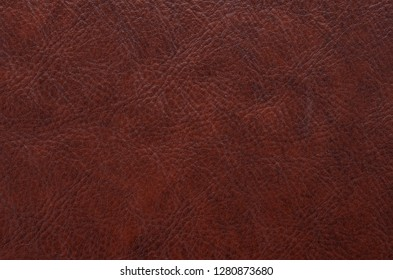 Red, brown leather, skin texture. Background rough, abstract.