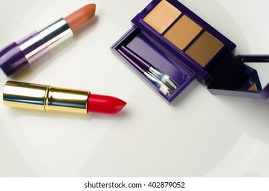 red and brown lipstick and shadow on the white background